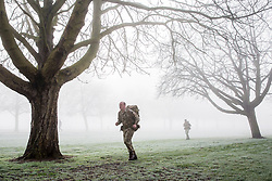 Windsor, UK. 31st January, 2019. Soldiers train in foggy conditions alongside the Long Walk in Windsor Great Park. There are two barracks in Windsor, the Victoria Barracks which currently houses the 1st Battalion Coldstream Guards and the Combermere Barracks which houses the Household Cavalry Regiment. Freezing fog patches are expected to clear slowly in south-east England during the morning, to be followed by cloud, sleet and snow in the east.