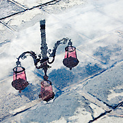 The reflection of an ornate street lamp in a puddle on a rainy day in Venice, Italy.<br />