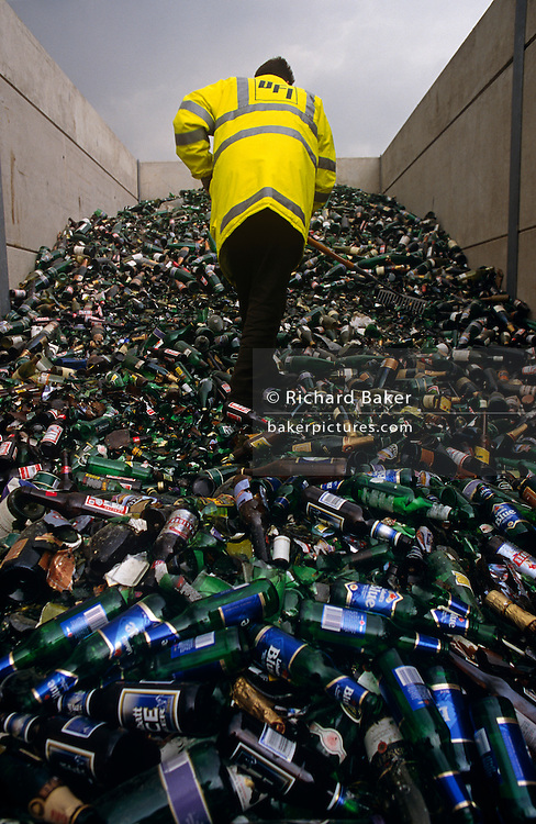 An employee of an unidentified recycling company used by BAA (British Airports Authority) rakes through a mountain of glass bottles, piled high in a depsitory near Gatwick Airport, Sussex England. The drinks from these branded bottles have been consumed at airport terminal buildings and other BAA property and the man dressed in a fluorescent safety jacket scrapes the containers in readiness for transportation to another facility. The picture is an upright and with such a wide-angle view, we see the bottles stretching from the closest to the lens to the far end of the compartment in a mound of materials destined for a machine that will crush and transform them into new glass.