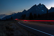 Tail lights in the night highway at Grand Teton National Park with background of mountain range and sun setting behind.