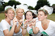 """Photo by Andrew Tobin/Tobinators Ltd - 07710 761829 - L-R Michelle Berry, Aimi Bresler, Emma Watson and Rachel Cross of the """"Brides to P"""" team pose for a photo during the World Peashooting Championships held at Witcham, Cambridgeshire, UK on 13th July 2013. Run in conjunction with the village fair, the Championships have been held in Witcham since 1971 when they were started by a Mr Tyson, the village schoolmaster, in order to raise funds for the village hall.Competitors come from as far afield as the USA and New Zealand to attempt to win the event. The latest technology is often used, including laser sights and titanium and carbon fibre peashooters. All peashooters must conform to strict length rules, not exceeding 12 inches, and have to hit a target 12 feet away. Shooting 5 peas at a plasticine target attached to a hay bale, the highest scorers move through the initial rounds to a knockout competition, followed by a sudden death 10-pea shootout."""