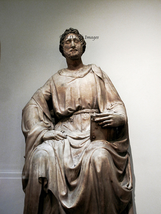 Marble statue of St. Luke, by Nanni di Banco, in the Museo dell'Opera del Duomo, Florence.  The work was on the original facade of the cathedral, which was redesigned and built.  The seated figure looks down on us with a supercilious sneer, holding a book on his knee with one hand.