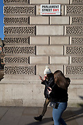 A man walks and looks at his phone beneath the signpost for Parliament Street SW1, Westminster, on 29th January 2020, in London, England.
