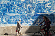 Young and old passing Azulejos Portuguese blue and white wall tiles of Capela das Almas de Santa Catarina  - St Catherine's Chapel in Porto, Portugal