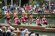 """Samoan dancers in the Canoe Pageant, """"Rainbows of Paradise."""" The Polynesian Cultural Center (PCC) is a major theme park and living museum, in Laie on the northeast coast (Windward Side) of the island of Oahu, Hawaii, USA. The PCC first opened in 1963 as a way for students at the adjacent Church College of Hawaii (now Brigham Young University Hawaii) to earn money for their education and as a means to preserve and portray the cultures of the people of Polynesia. Performers demonstrate Polynesian arts and crafts within simulated tropical villages, covering Hawaii, Aotearoa (New Zealand), Fiji, Samoa, Tahiti, Tonga and the Marquesas Islands. The Rapa Nui (Easter Island) exhibit features seven hand-carved moai (stone statues). The PCC is run by the Church of Jesus Christ of Latter-day Saints (LDS Church).For this photo's licensing options, please inquire."""