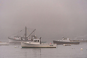Lobster boats moored in the harbor on a foggy morning in the quaint fishing harbor of Port Clyde, Maine.
