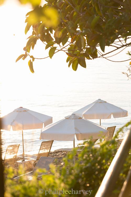 Beach umbrellas on seacoast at sunset, Neo Chorio, Cyprus