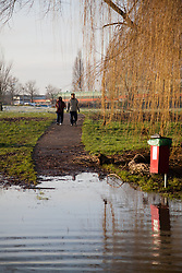 © Licensed to London News Pictures. 12/01/2014. Reading, Berkshire, UK. People out for a Sunday morning walk along the Thames Path in Reading, Berkshire. The River Thames has broken its banks causing extensive flooding. Photo credit : Rob Arnold/LNP