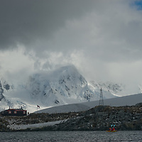 Kayakers paddle near Port Lockroy Museum on Goudier Island, near the Antarctic Peninsula, Antarctica. Mountains on Anvers Island are in the background.