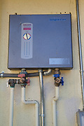 Tankless water heater on side of Green home that is off the grid. Solar power and a rainwater harvesting system supply all the energy and water for this home in Los Angeles, California, USA