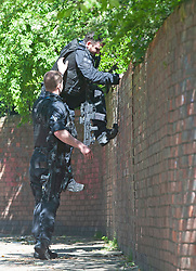 ©Licensed to London News Pictures 20/04/2020  <br /> Charlton, UK. A policeman jumping back over a high wall at the rear of the property. Metropolitan police officers surrounded a property near Charlton football club, Charlton, South East London today to arrested a suspect. The man who is believed to have been running from police was trapped in a back garden by at least ten armed police officers and a police dog.<br />  Reports on social media show footage of a white van in a high speed pursuit, it is not confirmed to be linked to this incident at the present time. Photo credit:Grant Falvey/LNP