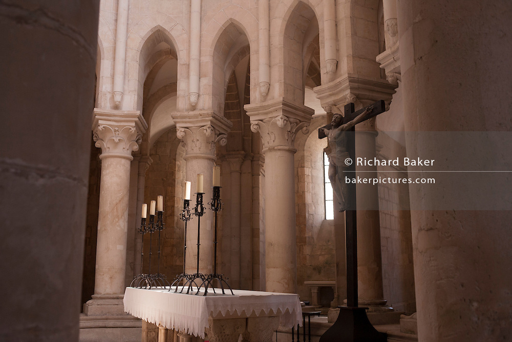 Beneath tall columns and pillars is the altar and crucifix in the central nave of Alcobaca Monastery (Mosteiro de Santa Maria de Alcobaca), on 16th July, at Alcobaca, Portugal. The monastery was completed in 1223 for the Cistercian order and added to further by King Dinnis (Dennis) who built the main cloister and is now a UNESCO World Heritage Site. Austere architecture is in keeping with the Cistercian regard for simplicity. (Photo by Richard Baker / In Pictures via Getty Images)
