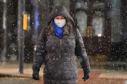 © Licensed to London News Pictures. 14/01/2021. Leeds, UK. A woman wears a face mask  as she walks in Leeds city centre during heavy snow this morning. Photo credit: Ioannis Alexopoulos/LNP