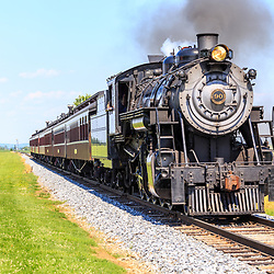 Strasburg. PA - June 19, 2016: Strasburg Rail Road Locomotive 90 pulls passenger cars through Lancaster County pastures.
