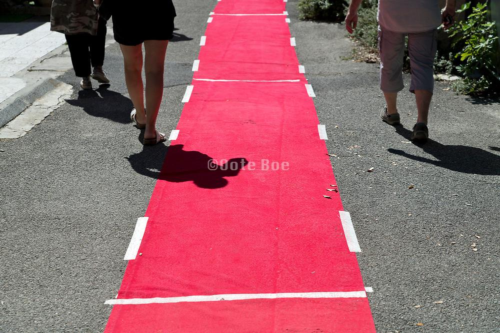 people walking beside the red carpet