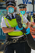 A Police officer holds the right leg of an arrested member of Extinction Rebellion Youth Cambridge who participated in a roadblock protest action outside Baringa Partners building in London on Thursday, Sept 10, 2020 - in an attempt to highlight the involvement of Schlumberger Limited in what they call 'ecocide'. Schlumberger is an oilfield services company working in more than 120 countries and has four principal executive offices located in Paris, Houston, London, and The Hague. An article at the Guardian suggests that it's ubiquitous in fossil fuel operations across the world, has more staff than Google, turns over more than Goldman Sachs, and is worth more than McDonald's – yet you won't have heard of it. XR Youth of Cambridge said that the British government gave 'Schlumberger' a no-strings-attached £150 million bailout loan as it was laying off a fifth of its global workforce. Another activist added: 'Schlumberger is hiding in plain sight here in Westminster. Every day, hundreds of people walk past this building with no idea that they're on the doorstep of a climate crime scene.'<br /> Environmental nonviolent activists group Extinction Rebellion enters its 10th and final day of continuous ten days protests to disrupt political institutions throughout peaceful actions swarming central London into a standoff, demanding that central government obeys and delivers Climate Emergency bill. (VXP Photo/ Vudi Xhymshiti)