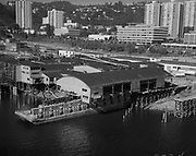 Ackroyd_18973-4. Lebeck and Son, Aerials warehouse on barge. August 2, 1974. (south Waterfront area south of the Hawthorne bridge. They are barging the entire 45,000 square feet Multnomah Plywood factory to its new home in St Helens.)