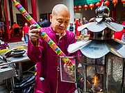 05 FEBRUARY 2019 - BANGKOK, THAILAND:  A man lightd incense sticks at Canton Shrine in Bangkok during Chinese New Year observances. Chinese New Year celebrations in Bangkok started on February 4, 2019, although the city's official celebration is February 5 - 6. The coming year will be the Year of the Pig in the Chinese zodiac. About 14% of Thais are of Chinese ancestry and Lunar New Year, also called Chinese New Year or Tet is widely celebrated in Chinese communities in Thailand.     PHOTO BY JACK KURTZ