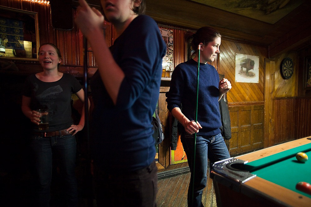 Young women mingle and play pool at the Dark Horse Bar and Grill in Boulder, Colorado.