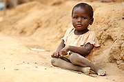 A toddler sits on the ground in the village of Popoko, Bas-Sassandra region, Cote d'Ivoire, on Sunday March 4, 2012.