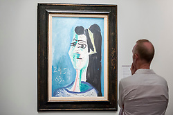 """© Licensed to London News Pictures. 28/06/2018. LONDON, UK. A visitor views """"Tête De Femme"""", 1963, by Pablo Picasso. Members of the public visit Masterpiece London, the world's leading cross-collecting art fair held in the grounds of the Royal Hospital Chelsea.  The fair brings together 160 international exhibitors presenting works from antiquity to the present day and runs 28 June to 4 July 2018.  Photo credit: Stephen Chung/LNP"""