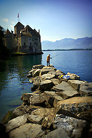 A man is standing on large rocks and fishing in Lake Geneva outside of the Chateau de Chillon in Montreux, Switzerland