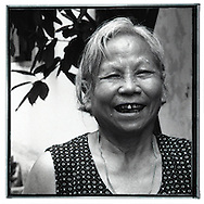 Portrait of an old vietnamese woman. Her face is quite wrinled. She smiles but teeth appears black and in very bad shape.