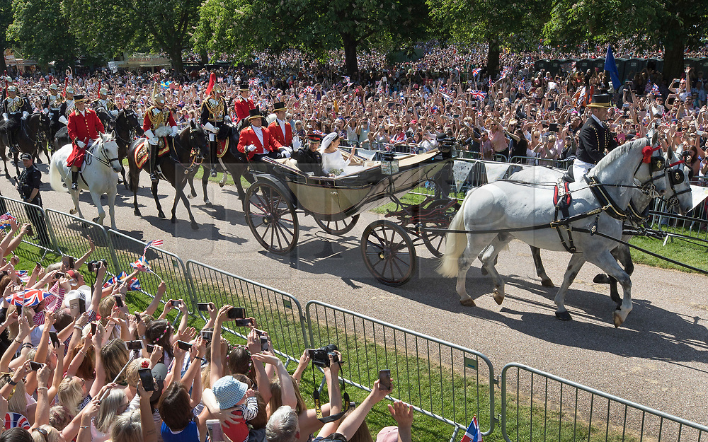 © Licensed to London News Pictures. 19/05/2018. Windsor, UK. The Duke and Duchess of Sussex ride in a carriage down The Long Walk back towards Windsor Castle after getting married in St George's Chapel, Windsor. Photo credit: Peter Macdiarmid/LNP