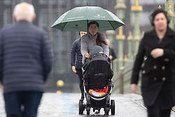 © Licensed to London News Pictures. 17/03/2021. London, UK. A woman shelters under an umbrella as she walks across Westminster Bridge during a rain shower. Rain is set to be replaced with cloudy cold conditions in London this afternoon. Photo credit: George Cracknell Wright/LNP