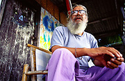 An old hippy traveller outside his beach hut on the island of Koh Pangan, Thailand