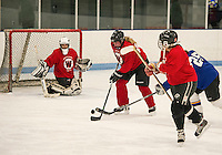 Lori Marsh of the Red team blocks a shot by Leslie Hoyt of the Blue team during Tuesday evening Lakes Region Womans Hockey Club at the Laconia Ice Arena.  (Karen Bobotas/for the Laconia Daily Sun)