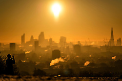 © Licensed to London News Pictures. 29/12/2016. London, UK. A woman takes a picture of sunrise over the city of London as seen from Parliament Hill on Hampstead Heath, Hampstead, North London on another cold winter morning. Most of the UK has woken to freezing temperatures. Photo credit: Ben Cawthra/LNP
