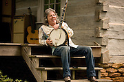 A musician and guitar maker sits on his cabin's front porch with his banjo.