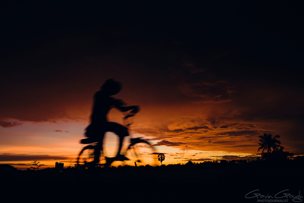 The silhouette of a man on a bicycle against a dark red sky at sunset, Bamboo Train, Battambang, Cambodia