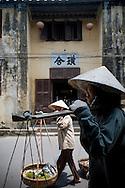 Two vietnamese woman walks in a street of Hoi An, Vietnam, Asia. They carry some fruits in their yoke. Deux femmes vietnamiennes transportent des fruits à l'aide de leur palanche.