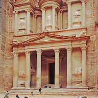 """Tourists walk past """"The Treasury,"""" a signature feature of Petra, a World Heritage Site in Jordan."""