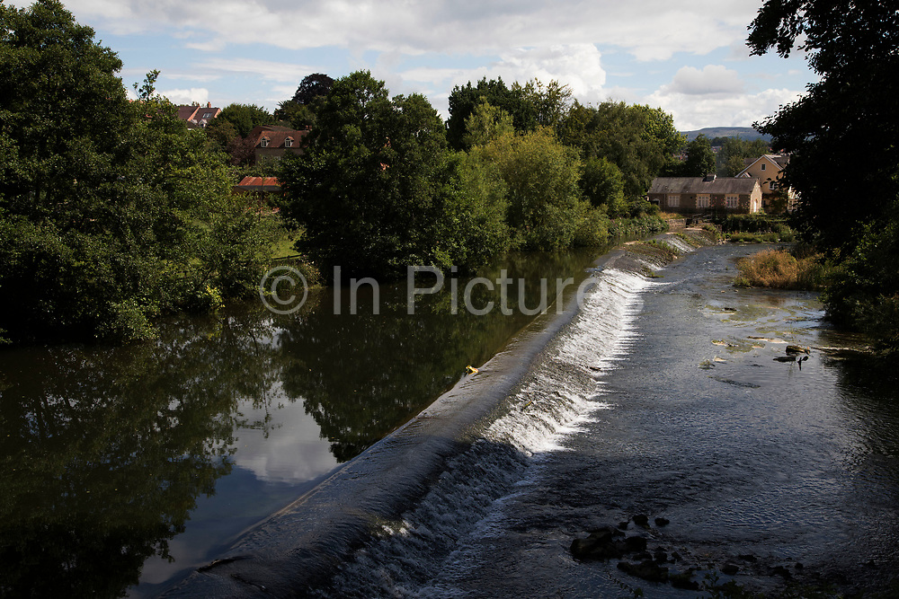 Looking over the weir on the River Teme towards Ludlow, United Kingdom. Ludlow is a market town in Shropshire, England. With a population of approximately 11,000, Ludlow is the largest town in south Shropshire. The town is near the confluence of two rivers. The oldest part is the medieval walled town, founded in the late 11th century after the Norman conquest of England. It is centred on a small hill which lies on the eastern bank of a bend of the River Teme. Atop this hill is Ludlow Castle and the parish church, St Laurences, the largest in the county. From there the streets slope downward to the River Teme.