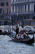 A group of people get a ride on a gondola with a gondolier steering the boat with a large oar, Grand Canal, Venice, Italy...Subject photograph(s) are copyright Edward McCain. All rights are reserved except those specifically granted by Edward McCain in writing prior to publication...McCain Photography.211 S 4th Avenue.Tucson, AZ 85701-2103.(520) 623-1998.mobile: (520) 990-0999.fax: (520) 623-1190.http://www.mccainphoto.com.edward@mccainphoto.com.