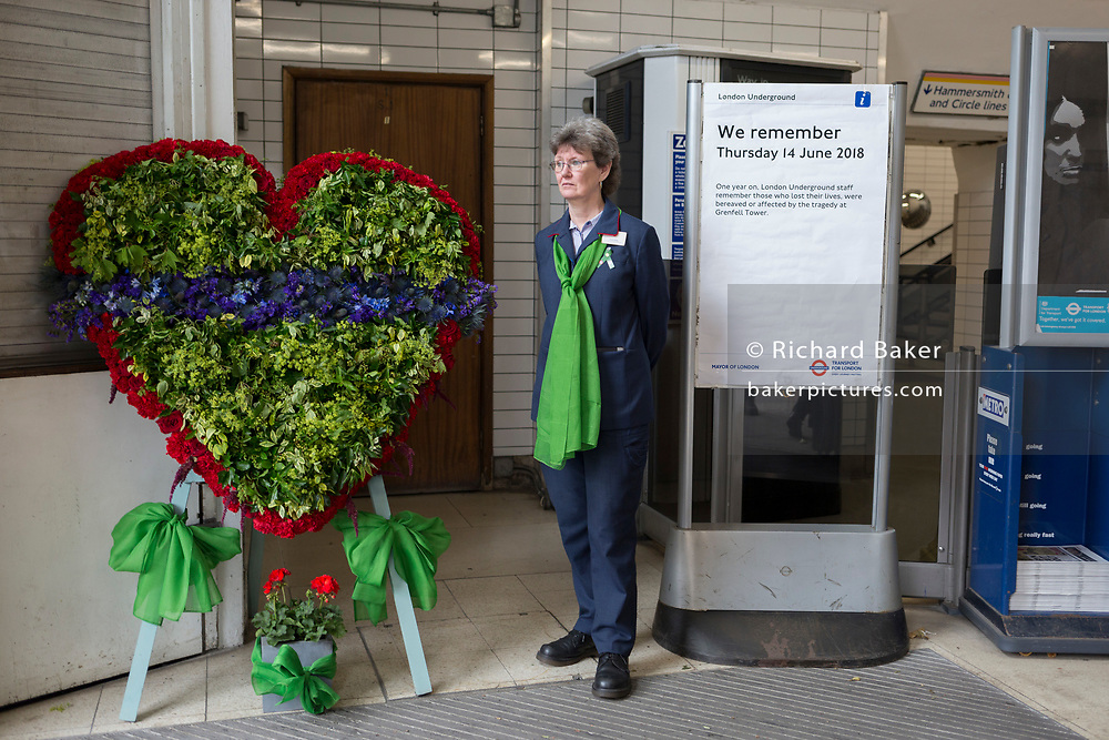 A memorial wreath at the entrance of Latimer Road tube station on the first anniversary of the Grenfell tower fire, on 14th June 2018, in London, England. 72 people died when the tower block in the borough of Kensington & Chelsea were killed in what has been called the largest fire since WW2. The 24-storey Grenfell Tower block of public housing flats in North Kensington, West London, United Kingdom. It caused 72 deaths, out of the 293 people in the building, including 2 who escaped and died in hospital. Over 70 were injured and left traumatised. A 72-second national silence was held at midday, also observed across the country, including at government buildings, Parliament.