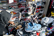 A shop worker eats his takeaway lunch while surrounded by his stock, a lot of trainers and other footwear in Deptford, on 22nd October 2021, in London, England.