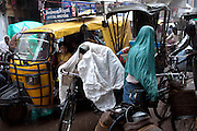 Under the heavy rain, a boy is sitting inside a rickshaw passing though a busy street of Varanasi, Uttar Pradesh, India.
