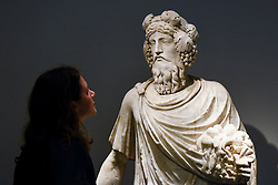 "© Licensed to London News Pictures. 25/06/2019. LONDON, UK. A staff member views ""Silvanus"" a 1st century AD Roman marble scuplture, from Galerie Chenel at a preview of Masterpiece London 2019, the world's leading cross-collecting art fair held in the grounds of the Royal Hospital Chelsea.  The fair brings together 157 international exhibitors presenting works from antiquity to the present day and runs 27 June to 3 July 2019.  Photo credit: Stephen Chung/LNP"