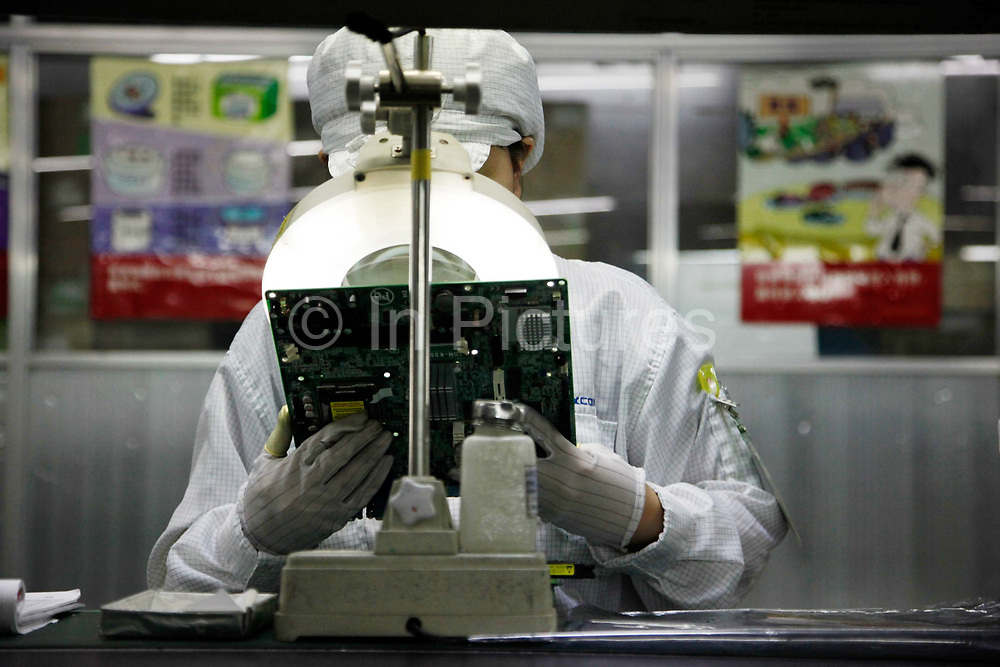 Employees work on the assembly line at Hon Hai Group's Foxconn plant in Shenzhen, China, on Wednesday, May 26, 2010. Hon Hai is the parts supplier for many hi-tech companies around the world including Apple Inc., Hewlett-Packard Co. and Dell Inc. There have been 12 suicides at the company's 300 thousand employee strong factory complex in Shenzhen so far this year. Foxconn has since moved some of its operations further inland to be closer to labor pool as well as cut costs.