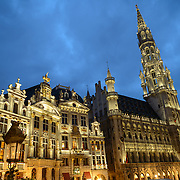 Hotel de Ville in the Grand Place, Brussels, at dusk. Originally the city's central market place, the Grand-Place is now a UNESCO World Heritage site. Ornate buildings line the square, including guildhalls, the Brussels Town Hall, and the Breadhouse, and seven cobbelstone streets feed into it.