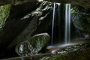 A tiny waterfall flows through a talus cave located next to the Index Town Wall near the town of Index, Washington. Talus is a pile of rocks that broke off a nearby mountain face. Occasionally the rocks break off and land in such a way that it forms a natural cave. The falls is illuminated by a skylight in the cave.