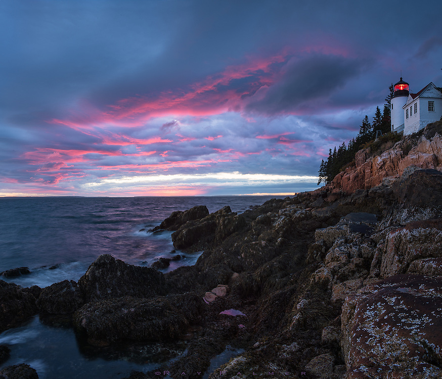 Bass Harbor Head Lighthouse, Acadia, Maine.   I was kind of late.  I couldn't pass by an estuary a ways back, where the evening light was just right, seen from a small bridge just high enough to capture the just right S curve of the water disappearing into the wetland.  Approaching the headland here, surrounded by forest, the cloud cover didn't give me any expectations.   But when I came out of the woods into the open and started down the cliffs, I could see that the gap on the horizon was enough for a light show--the sky was just pinking up, and I started to panic at missing it.   And so I risked life and limb clambering over seaweed-slick and muscle-encrusted boulders to get to a spot where all the other photographers wouldn't be in my frames, and myself not in theirs.  The buoy bell behind me intoned heavily as it was swept up and back with each passing wave, and the very sky seemed like a beacon to the harbour, situated on the other side of this headland.  How does the lightkeeper deal with it, I wondered...manning the red beacon whose glimmer can be seen 13 miles away, to welcome the ships at sea to safe refuge.  A thankless job.  Always there for them, but never the destination.  I can relate.  I imagined myself a harbour of sorts.  I presumed, wrongly, that there was safety in the arms of my sanctuary, and I would take care of a ship in rough seas.  But the lamp that shone so strongly steered the ship away, for I was just a light, not the harbor.  When the skies deadened I left, and the light still burned.