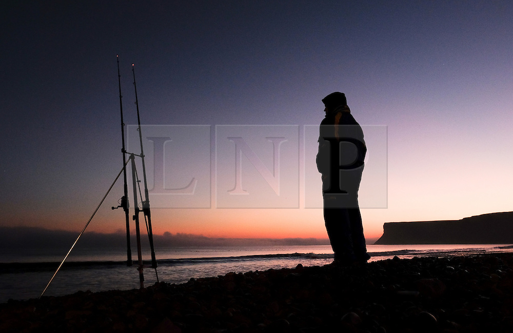 © Licensed to London News Pictures.02/11/15<br /> Saltburn, UK. <br /> <br /> A fisherman watches his lines as a heavy fog bank sits out at sea from the Cleveland coast.<br /> <br /> Photo credit : Ian Forsyth/LNP