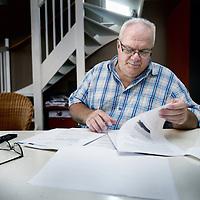 Nederland, Hoofddorp , 5 augustus 2013.<br /> Ondernemer en raadslid Rinus Beusenberg thuis achter de papieren.