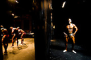 For two years in a row, in a rundown theater in Porto, the Portuguese National Championship of Bodybuilding WABBA happened. Several athletes, from allover the country came to this one day competition. <br /> These are photos from the backstage, where the athletes exercise and get body paint for the stage presentation. The muscles and the gold and brown colors get ready in the confusion of tubes, abandoned wood from different theater plays, photos from the past and dressing rooms with 100 years old. Mário posing behind the stage.