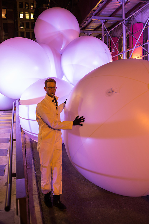 A handler stands by inflated balls on Jersey Street near the corner of Mulberry Street, part of the Ideas City performance by Snarkitecture.